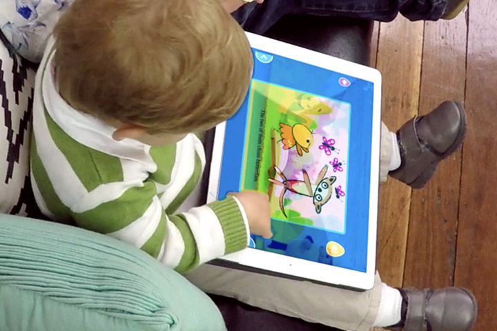 Toddler playing a Reading Eggs Junior activity on a tablet